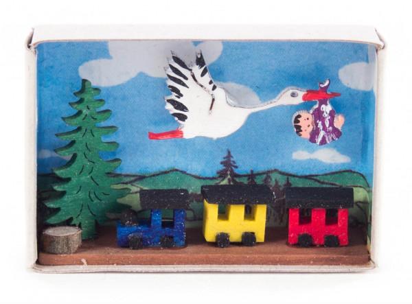 Dregeno Erzgebirge - Zündholzschachtel mit Storch, Baby und Eisenbahn
